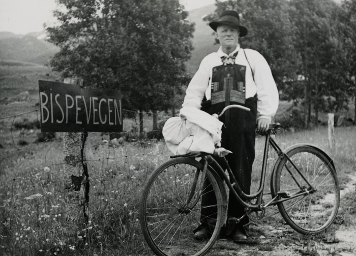 "Elisabeth Meyer, Man with bicycle, Left - a sign for ""Bispevegen"", Photographs from Setesdal around 1940-42, Gelatin silver print, baryta, NMFF.002574-24"